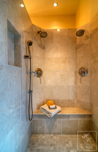 LIMESTONE TILED SHOWER WITH MULTIPLE SHOWER HEADS